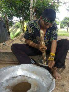 Kaxinawa Indian sitting on his patio grinding tobacco with a pestle and mortar to make Shamanic snuff