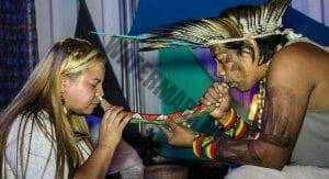 indigenous Brazilian applying sete ervas rapé to a woman