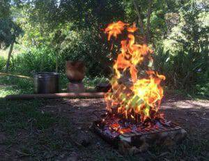 place in nauture with a fire in the foreground and tools in the background, burning bark for samaúma ash