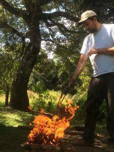 man putting his fire stick in the fire pit where bark burn for the production of Caneleiro ash (Cenostigma macrophyllum)