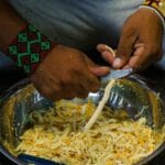 close up of 2 hands one holding a knife, shredding Sananga root, Tabernaentana Undalata, Tabernaentana Sahanho