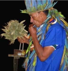 Kamëntsá Taita Alfredo Juajibioy playing harmonica during a ritual